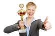 Lachende Frau mit Pokal hält Daumen hoch