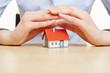 Hände halten schützend Dach über ein Haus