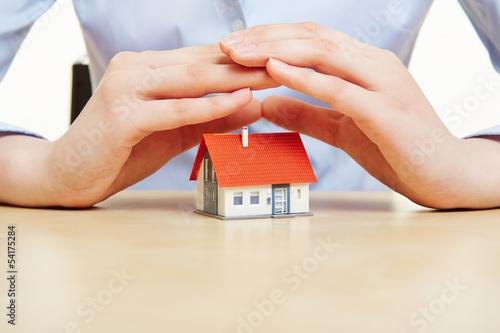 Hände halten schützend Dach über ein Haus - 54175284