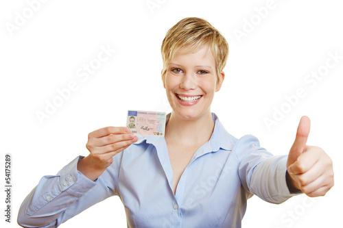Frau zeigt Führerschein und hält Daumen hoch