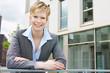 Lächelnde junge Geschäftsfrau vor Gebäude