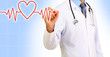 Medical doctor draws cardiogram on blue background