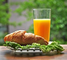 Свежий круассан и стакан апельсинового сока