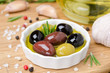 bowl with different olives in olive oil and spices on a wood