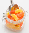 orange and lemon jelly beans in glass jar with scoop