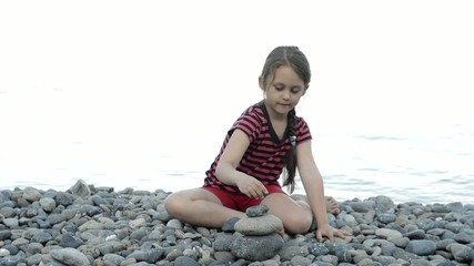 girl on the beach adds a pyramid of pebbles