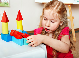 Child preschooler play wood block in play room.