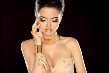 Fashion photo of beautiful brunette woman posing in golden jewe