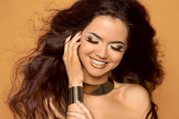 Happy smiling woman with makeup and blowing curly hair, studio p