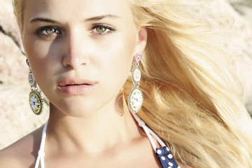 beautiful mysterious blond young woman. stone background
