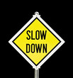 Slow Down yellow road sign isolated over black