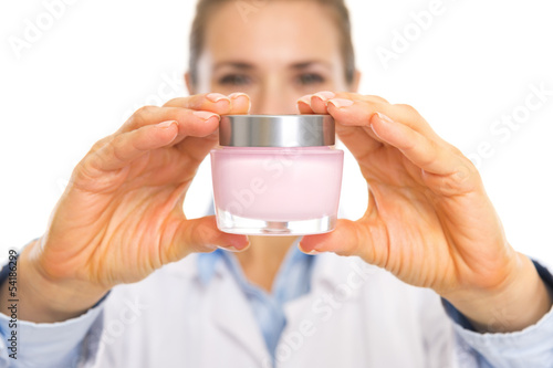 Closeup on cream bottle in hand of cosmetologist