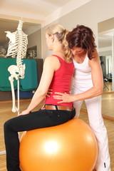 Physiotherapeutin mit Patientin an Lendenwirbelsäule