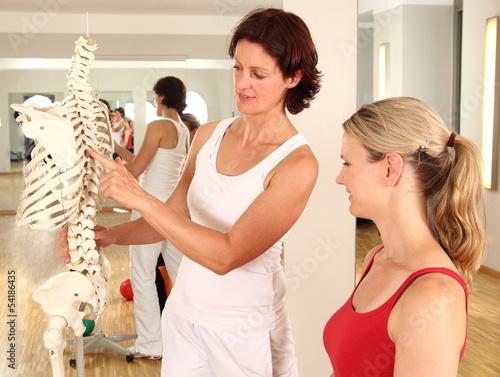 Physiotheraeutin erklärt Patientin Wirbelsäule - 54186435