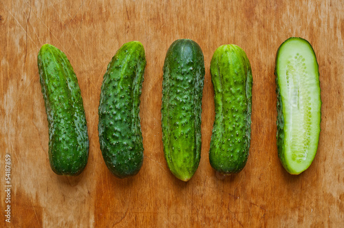 Cucumbers on a wooden table, one sliced