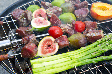 Lamb shashlik (grill) with figs, asparagus and tomatoes during p
