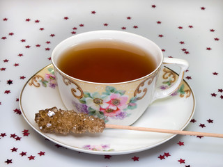Cup of tea with sugar stick in antique crockery