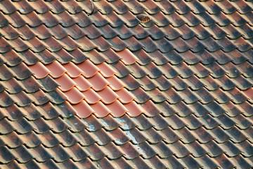 Alte Dachziegel umgeben neue Dachziegel