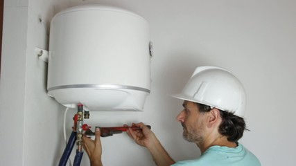 plumber with pipe wrench connecting pipes