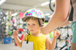 Adorable girl fitting bike helmet in sport store