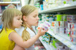 Mother with daughter on back select products in supermarket