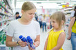Young mother with daughter select milk drinks in supermarket