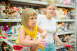 Adorable girl in shopping cart with mother on back select toys i