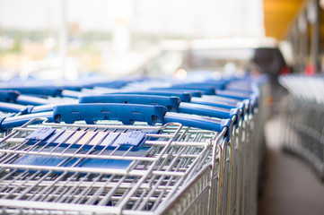 Rows of blue shopping carts on entrance of supermarket