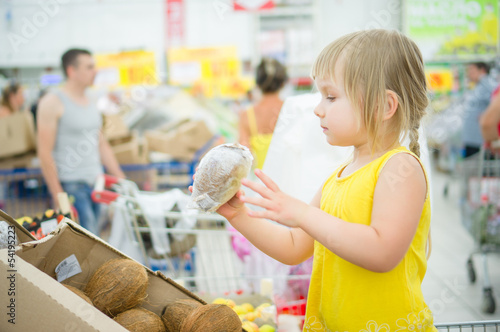 Adorable girl stay in shopping cart and select coconuts