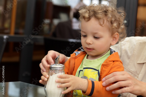 Toddler holding sugar bowl