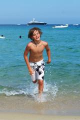 Junge läuft durchs Wasser