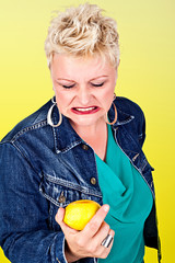 Portrait of middelaged beautiful woman eating fresh lemon