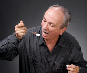 Man eating pills with a spoon