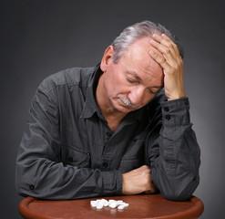 Senior man looking at pills