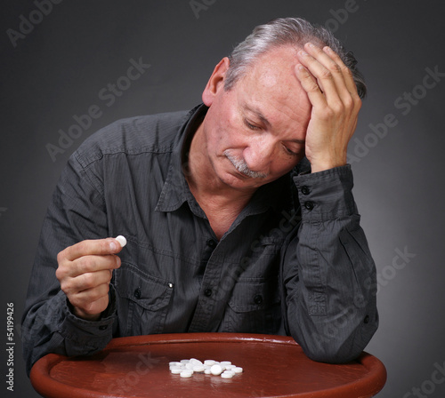 Senior man looking at pills