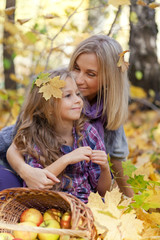 Happy mum and the daughter play autumn park