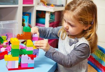 bambina che gioca con le costruzioni