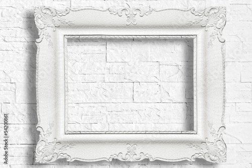 White baroque frame on modern brick wall