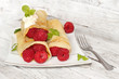 Delicious pancakes with raspberries on the wooden table