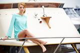 Elegant retro woman wear  dress , sitting near the wooden yacht.