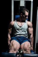 bodybuilder doing heavy weight exercise for legs on machine leg