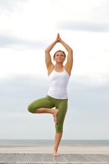 Woman standing on one leg in balance yoga pose