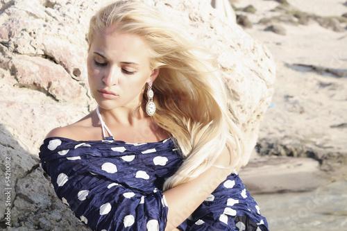 beautiful blond woman.stone blue polka dot scarf.rock by sea
