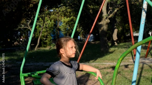 little girl on a children's swing