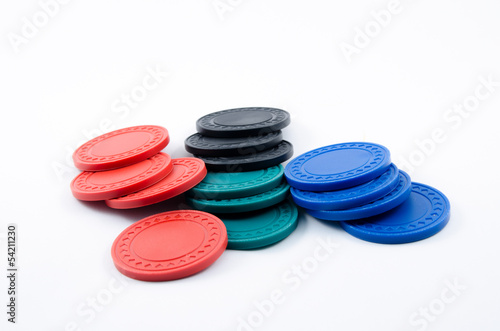 Fallen over stacks of poker chips in black, blue, green and red