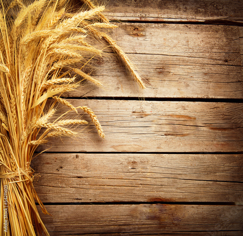 Leinwanddruck Bild Wheat Ears on the Wooden Table. Harvest concept