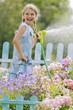 Garden -  girl watering roses with garden hose