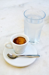 White espresso cup and glass of cold water on the marble table