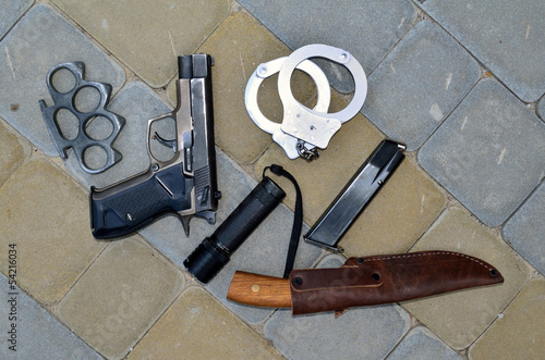 pistol, brass knuckles, handcuffs and a knife