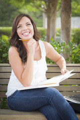 Pretty Female Student Smiling with Books on a Bench on Campus